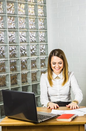 topicality: Laughing business woman with laptop in office
