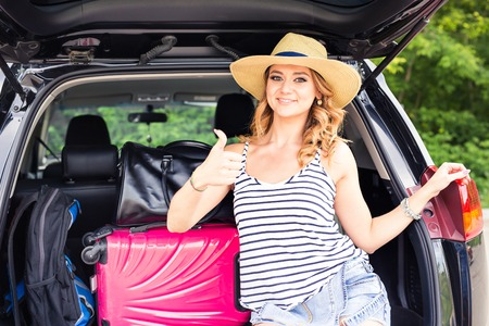 young leave: Travel, tourism - Girl ready for the travel for summer vacation. Young female sitting in the trunk of a car with suitcases, showing thumb up sign, ready to leave for vacations