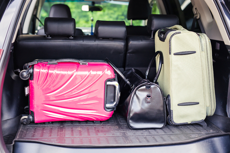 to depart: Suitcases and bags in trunk of car ready to depart for holidays.