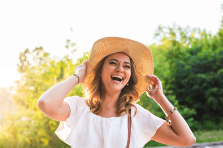feeling happy: Beach woman laughing having fun in summer vacation holidays. Girl wearing big straw hat.