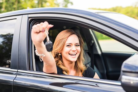 new automobile: Woman driver holding car keys driving her new automobile Laughing young girl.