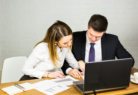 conversating: Two entrepreneurs sitting together working in an office desk comparing documents