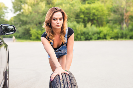 tire: Young beautiful Woman changing tire on a road