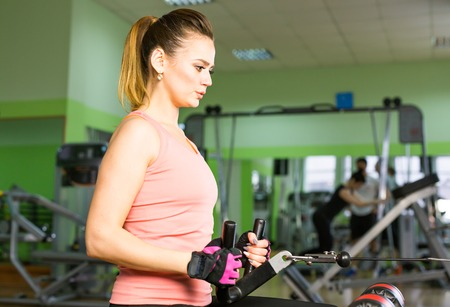 exercitation: The woman shakes her muscles on the simulator in the gym Stock Photo