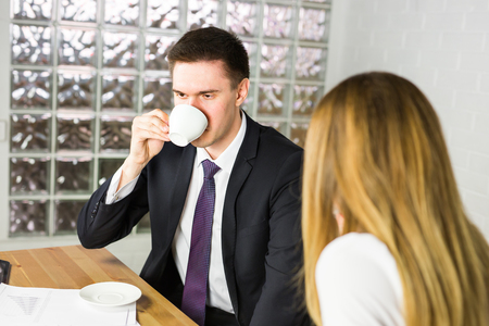 moneymaker: Portrait of handsome successful man drink coffee and look to the digital tablet screen sitting in coffee shop, business man having breakfast sitting on beautiful terrace with plants Stock Photo