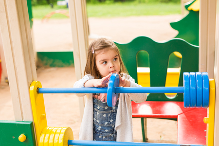 Little girl on a playground. Child playing outdoors in summer. Kids play on school yard. Happy kid in kindergarten or preschool. Children having fun at daycare play ground. Toddler on a swing. 版權商用圖片 - 59453890