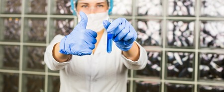 technologist: female lab technician giving a thumbs up of success while holding up a test tube in her gloved hand. Stock Photo