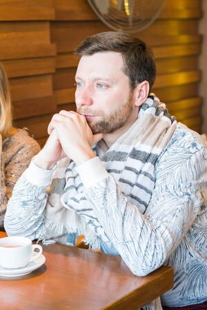 Pensive young man sitting in coffee shop
