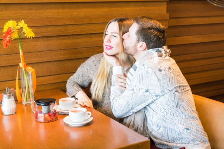 cheek: Young man kissing her girlfriend in the cheek while having some tea together in a cafe.
