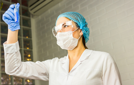 medical professional: Scientific researcher holding at a liquid solution in a lab