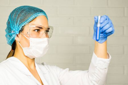 research science: Investigator checking test tubes. Woman wears protective goggles.