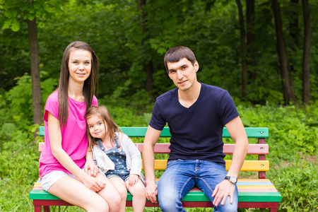 tog: Portrait of a smiling couple with young kids sitting on park bench Stock Photo
