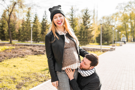 Family together in the autumn park. Woman is pregnant.