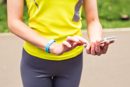 Woman using fitness bracelet during morning run.