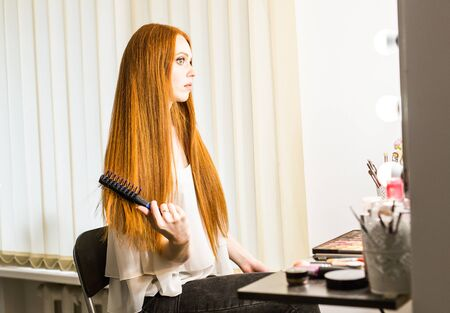 split lip: beautiful redhead girl with comb in salon Stock Photo