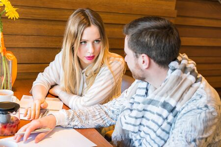 strained: Male and female business colleagues working together on a hard problem at indoors cafe. They have strained expression on their faces