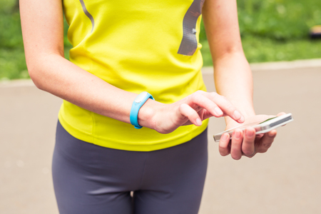 resting heart rate: Hand wearing a fitness tracking armband indoors