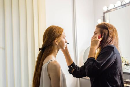 stylist: Stylist is talking on the phone while doing make-up.