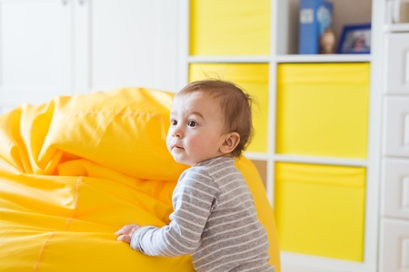 Beautiful adorable laughing baby boy infant face. Smiling child sits on a chair
