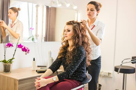 Professional hairdresser styling long woman curly hair. Stock Photo