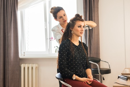 hair do: Reflection of hairdresser doing hair style for woman in hairdressers. Concept of fashion and beauty Stock Photo