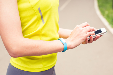 Hand wearing a fitness tracking armband indoors