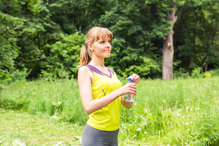 Fitness woman drinking water after work out exercising on summer outdoor portrait.