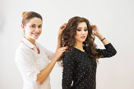 finishing: beauty, hairstyle and people concept - happy young woman with hairdresser finishing hairdo at salon.
