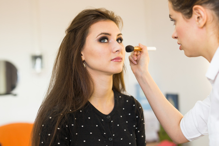 Make-up artist doing make up for young beautiful woman. Stock Photo