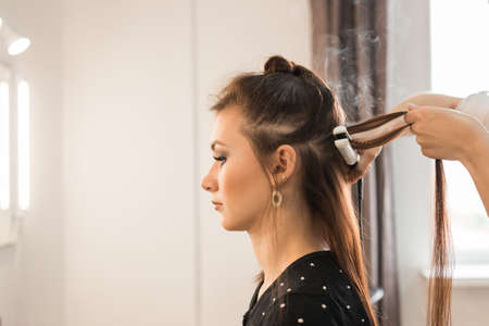 jornada de trabajo: working day inside the beauty salon. Hairdresser makes hair styling