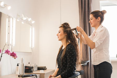 hair curler: Woman at hairdresser with iron hair curler Stock Photo