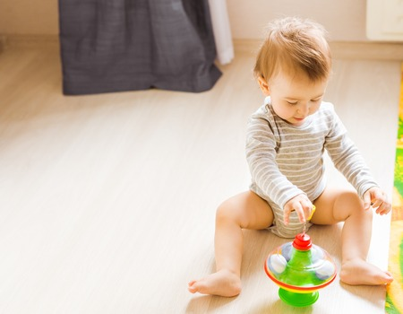 baby boy playing with toy indoors at home. Standard-Bild
