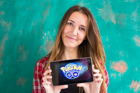 hit tech: Ufa, Russia. - July 29: Woman show the tablet with Pokemon Go logo