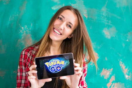 Ufa, Russia. - July 29: Woman show the tablet with Pokemon Go logo