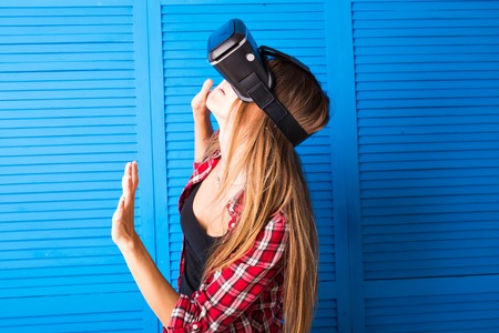 Young woman getting experience using VR-headset glasses of virtual reality much gesticulating hands. Imagens