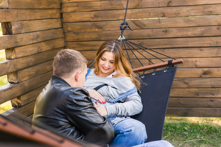 Expectant young loving couple on hammock outdoors