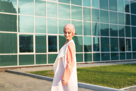 inhabit: girl in abaya on the background of the business center.