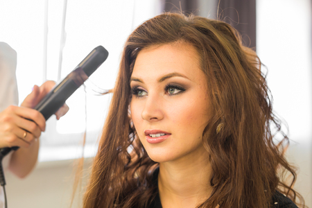 curler: Woman at hairdresser with iron hair curler Stock Photo