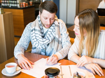 stumped: Male and female business colleagues working together on a hard problem at indoors cafe. They have strained expression on their faces