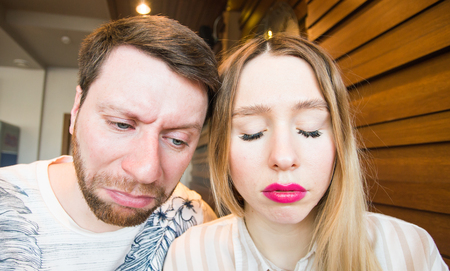 stupidity: young loving couple grimacing indoors, sad faces Stock Photo