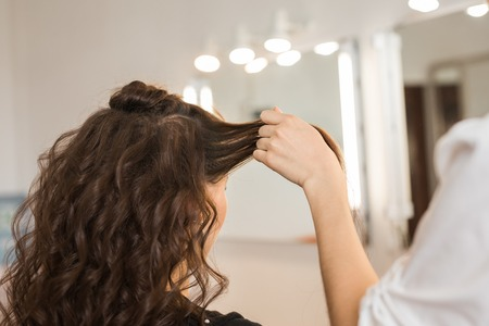 Closeup woman hairdresser coiffeur makes new hairstyle.