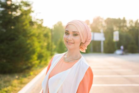 sunni: Young woman wearing hijab head scarf in city