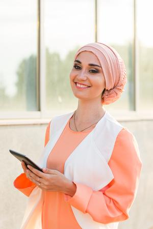 タブレット コンピューターの屋外で美しいアラビア少女 写真素材