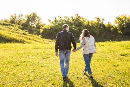 walking away: Couple Holding Hands Walking Away. stylish couple on sunny grass Stock Photo
