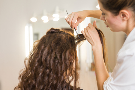 coiffeur: Closeup hairdresser coiffeur makes hairstyle for young woman