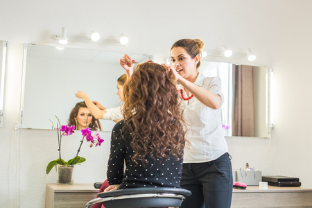 hairdresser parlor: Beautiful young hairdresser giving a new haircut to female customer at parlor.