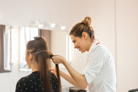 coiffeur: Hairdresser coiffeur makes hairstyle for young woman