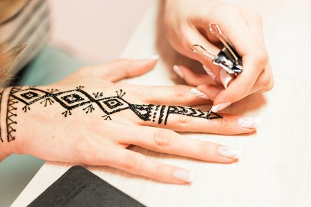 sanskrit: Drawing process of henna menhdi ornament on womans hand.