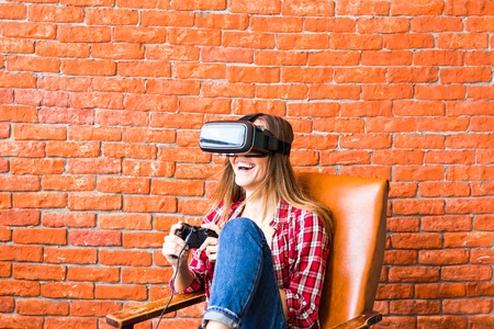 mediated: 3d technology, virtual reality, entertainment and people concept - happy young woman with virtual reality headset or 3d glasses playing game and fighting Stock Photo