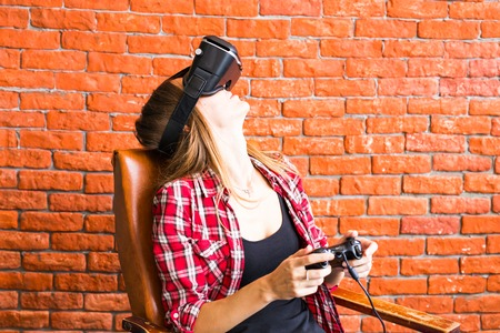 Smile happy woman getting experience using VR-headset glasses of virtual reality much gesticulating hands. Imagens